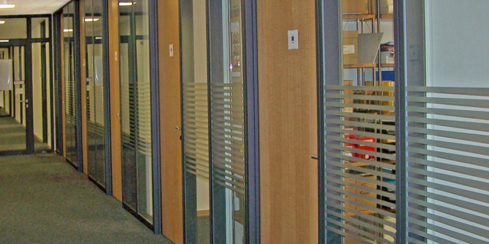 Partition wall with integrated doors, clad with timber.